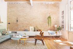 Salón con pared de ladrillo, mueble bajo blanco, sofá azul y alfombra con…