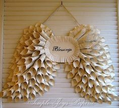 Angel wing wreath from book pages -- beautiful. Roll the newspapers or whatever papers you decide to use, and glue to cardboard.
