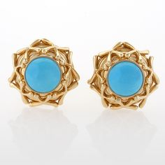 Turquoise and Gold Earrings by Schlumberger/Tiffany & Co  A pair of Estate 18 karat gold and turquoise earrings by Schlumberger. The circular earrings center on a turquoise cabochon that is surrounded by crossover gold wire work.