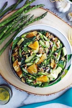 Asparagus Orange Spinach Salad with Basil Lemon Vinaigrette in a wooden bowl; asparagus to its side.