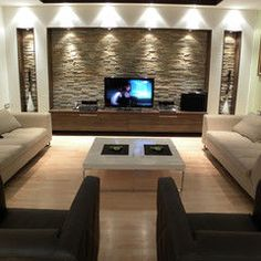 i like the lit accent wall in stone and the cutout niches finished in wood. also like the built-in countertop.