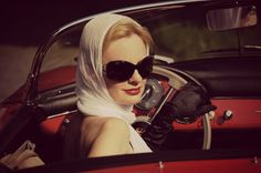Ride in a convertible wearing a scarf over my hair, oversize tortoiseshell sunglasses, and bright red lipstick.