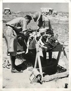 1942- Doctors tend a wounded British soldier on an emergency operating table at a station of the Royal Army Medical Corps in the Libyan desert.