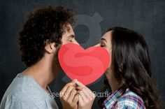 Couple Kissing Behind Paper Heart