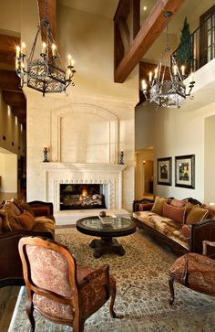 Velvety, deep-colored furniture and candle-shaped light fixtures haning from heavy rustic wood beams adds to the castle feel of this Mediterranean-style home.
