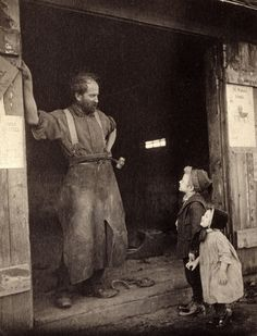 Two children talk to a blacksmith standing in the doorway of his forge, c. 1900.