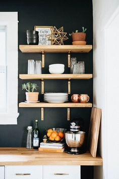 Black/White/Wood - Black walls, wood shelves, white cabinets, and gold accents. Great example of how to decorate open shelving in a kitchen.