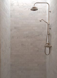 Subway carrara white marble tile with exposed pipe shower system. Love the natural light.