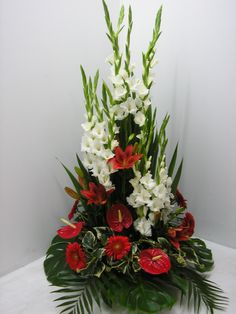 Planters for the wedding aisle. Use the white gladiolas and add calla lilies, some white orchids and some white roses. The red tropical flowers are to be white instead. Gladiolus Arrangements, Tropical Floral Arrangements, Christmas Flower Arrangements, Unique Flower Arrangements, Funeral Flower Arrangements, Christmas Flowers, Exotic Flowers, Tropical Flowers, Pretty Flowers