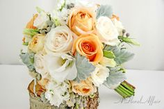 Blend different shades of roses with the silvery leaves of dusty miller for a beautiful garden effect.  Here we've mixed yellow/orange roses, champagne garden roses, ivory vendella roses, and ivory spray roses with white lisianthus, dusty miller and brunia.  Flowers by A Floral Affair #pdxweddings #weddingbouquet