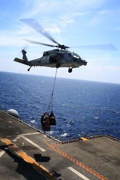 USS Boxer, At Sea - U.S. Marines with 13th Marine Expeditionary Unit and U.S. Navy H-60 helicopter crewmembers, conduct a vertical lift to transport a joint task force enabler from aboard USS Boxer to USS New Orleans, Oct. 10, 2013. Marines and Sailors are forward deployed for several months in support of theater requirements of geographic combatant commanders. (Official U.S. Marine Corps photo by Sgt. Jennifer Pirante/Released)