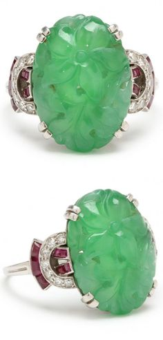 Art Deco Platinum, Jade, and Diamond Ring, Ellis Bros.  the oval jade carved in floral motif and set to the center in a four pair fancy prong mount and accented with (14) pavé set single cut round diamonds weighing approx .21 carat  and (14) channel set faceted red rubies, stamped platinum and signed by maker.