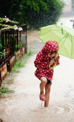 Girl dressed for rain, jumping in the puddles