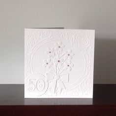 50th birthday card using Xcut embossing folder, Memory Box blushing bouquet die and Tattered Lace elegant numbers.
