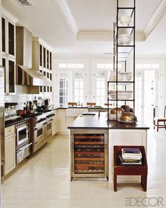 An antique etegere adds a vertical dimension and extra storage in this kitchen. Designer Darryl Carter.