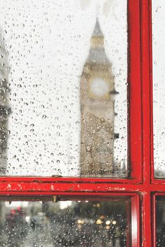 Dia lluvioso en Londres. Las gotas de agua desdibujan la Torre del Parlamento en el reflejo en una de las clasicas cabinas rojas de telefono
