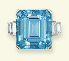 AN AQUAMARINE AND DIAMOND RING   The rectangular-shaped aquamarine weighing 21.19 carats to the baguette-cut diamond stepped shoulders and plain hoop