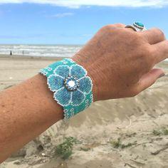 Découvrez ce bracelet très années 60 avec sa grosse fleur bleue turquoise avec son coeur de strass, tissé en perles miyuki. Chic et bohème, très léger et agréable à porter.