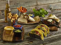 Tex-Mex Tacos on stands sweet potato fries and Mexican wraps on a range of  wood, cast iron and stainless steel
