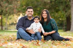 family of three with 1-year old toddler boy sitting among autumn leaves during a photo session - oakville baby photographer