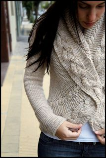 A seamless cabled cardigan, with an A-line shape, reversible shawl collar and set-in sleeves.