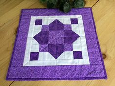 """Charming handmade square purple quilted table topper is an attractive centerpiece for a dining table, side table, night stand, or patio table. Doubles as protection from knick knacks, lamps, etc.  The square geometric patchwork quilt top is made with two purple print fabrics and white accent fabric. I used the darker purple fabric for both the backing and the hand stitched double binding.  Measures 15 1/4"""" square"""