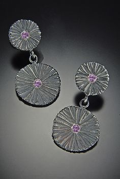 """Double Shield Earrings created by Dahlia Kanner using the lost wax technique, these sterling silver earrings have a dark patina that emphasizes their appealing organic texture. Pink sapphires serve as colorful focal points."""