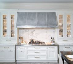 Beautiful white kitchen with floor to ceiling kitchen cabinets paired with marble countertops and marble slab backsplash. Glass-front kitchen cabinets flanking kitchen cooktop. Zinc kitchen hood, gas cooktop and stainless steel cooktop counters.