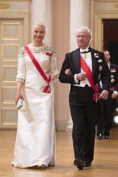 King Carl Gustaf of Sweden and Crown Princess Mette-Marit of Norway link arms as they enter the palace's celebrations. The Norwegian Princess looked stunning in a sweeping white gown with colourful floral detail around the collar. She kept her blonde hair neat in a slicked-back up 'do and completed her outfit with dazzling drop earrings and a clutch bag.