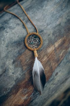 """The 'Original Spirit' Dreamcatcher Necklace is the ultimate accessory, adding a touch of uniqueness to any outfit! Handcrafted, this longer leather necklace features a 2"""" dreamcatcher with beautifully colored stones and a lovely feather. Necklace color choices include white, cream, natural (tan), brown, and black."""