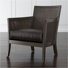 A dark grey wash and lustrous leather add a sophisticated note to Blake's breezy appeal. Crafted of teak and handwoven rattan panels, the chair hosts a deep, thick cushion upholstered in full-aniline leather finished with a beautiful, aged patina.
