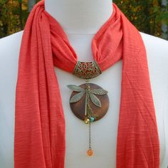 "High quality rayon jersey fabric that has a wonderful drape. These scarves will transform any outfit and make it ""pop"" with a bit of color and a stylish pendant. Burnt orange fabric features a layered pendant featuring a wood circle, bronze dragonfly and several chains of beads. They are a full 72"" long so you can wear them choker style at the neck or pull the pendant down for a longer scarf necklace. You can bring the ends around again and drape down your back. The options are endless."
