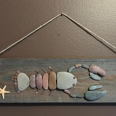 Pebbles and seaglass make a fun DIY artwork for a beach cottage!