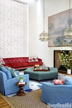 """In the living room, Warner conjures a fresh take on classic red, white and blue. The 14-foot-long vintage sofa is from the owners' previous residence. The chairs and smaller sofa are covered in a Groundworks fabric, and the wallpaper is by Jim Thompson. A Stark indoor-outdoor rug is topped by a custom Merida rug that was designed by Warner and inspired by inkblots. """"I painted a watercolor, played with it in Photoshop and sent it off,"""" she says."""
