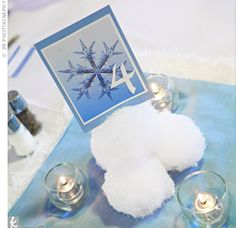 So adorable for a winter wedding!    Keeping with the winter theme, fabric squares, a snowflake-printed table card, and a mound of snowballs (made from Styrofoam, quilt batting, and diamond dust) took the place of floral arrangements on the tables.