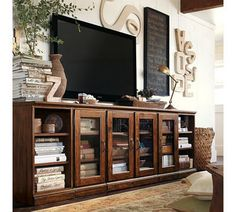 A robust cabinet, soft natural colors, books and plants as humble decorations. It all fits together. Tv watching for pro's.