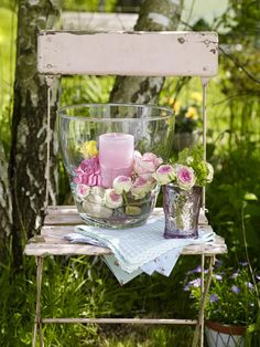 Place a candle and flowers in a large cylinder vase, a few flowers in a bottle, some vintage style napkins on a rustic chair for a lovely outdoor setting. #flowers #vignette #styling