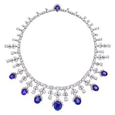 Harry Winston Sapphire & Diamond Fringe Necklace in platinum, composed of seven graduated oval-shaped sapphires with a part circular-cut diamond surround alternating with a pear and circular cut diamond trefoil fringe on a single line pear and circular-cut diamond riviere line. Signed Harry Winston. Of royal provenance.