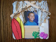 Three sizes of craft sticks are glued onto a paper template for base of frame. The roof is covered with fishing net and surfboards and flip flops cut from foam sheets are added. A magnetic strip is attached to back of frame.
