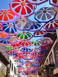 A main shopping street in Agueda, Portugal is covered by a canopy of colorful umbrellas as part of a city-sponsored art installation for the month of Umbrella Cover, Umbrella Art, Under My Umbrella, Colorful Umbrellas, Umbrellas Parasols, Umbrella Street, Instalation Art, Graffiti, Floating