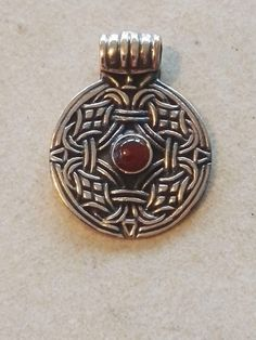 Vedhæng. Mariesminde. Bronze  m. rav: 100 kr.  27 x 21 mm -   Rundt hængesmykke fundet ved  gården Mariesminde ved  Langeskov på Fyn. Smykket blev fundet uden sten,  dette er det pyntet med ægte  naturrav. Originalen er udstilllet på  Vikingemuseet Ladby Smykket er dateret til ca. år 925.