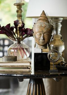 groundcovers: Artwork and oddities find a home on an antique Chinese pedestal table. A statue of a head from Thailand lends a dose of zen to the living room.