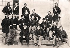 "Among the officers posing at Fort Laramie's Bachelor Officers Quarters, known as ""Old Bedlam,"" appears Caspar Collins (second from left, standing in front row). The aggressive infantry lieutenant lost his life on July 26, 1865, when he led 25 men against roughly 1,000 to 3,000 Indians, just outside Wyoming's Platte Bridge.  – Courtesy Wyoming State Archives and Historical Department –"