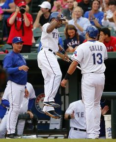Texas Rangers third baseman Joey Gallo (13) is congratulated by teammate Delino DeShields (7, center) and welcomed by manager Jeff Banister (left) after scoring his first major league run in the first inning against the Chicago White Sox at Globe Life Park in Arlington, Tuesday, June 2, 2015. (Tom Fox/The Dallas Morning News)
