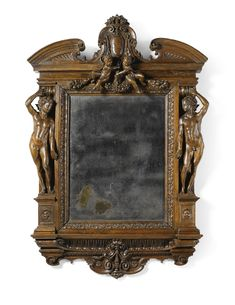 An Italian carved walnut frame, Florentine -  second half 16th Century -  the rectangular plate within a frame carved with foliage and standing nude male figures, the fluted base centred by a grotesque mask, the broken scrolled cresting centred by a coat-of-arms flanked by cherubs suspending fruiting swags, now inset with a mirror 146cm high., 99cm. wide; 4ft. 9½in., 3ft. 3in.