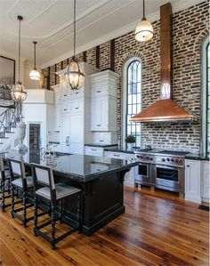 I love this loft kitchen. Love the gorgeous wood floors, the brick wall, the black island with black granite counters. Love the windows, but most of all, I love that awesome copper hood and exposed brick! Dream Kitchen, House Design, Home, Kitchen Remodel, House, Home Kitchens, Interior, Loft Kitchen, Kitchen Design