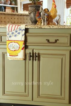Savvy Southern Style: Kitchen Cabinets Tutorial.  This also show a picture with white cabinets on top with the lower cabinets in the sage.  also love the backsplash!