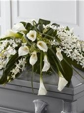 Casket Spray of white Dendrobium orchids, white calla lilies, green hydrangea and a variety of greens.