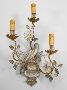 Pair of French 1940s mirrored glass and gilt metal 3 scroll arm wall sconces with parrot perched on urn backplate with floral decoration. $15,500