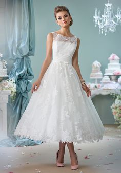 Sleeveless tea-length lace over tulle A-line dress with lace illusion bateau neckline, lace illusion back with covered buttons, natural waist belt with center bow, full skirt with scalloped hem.